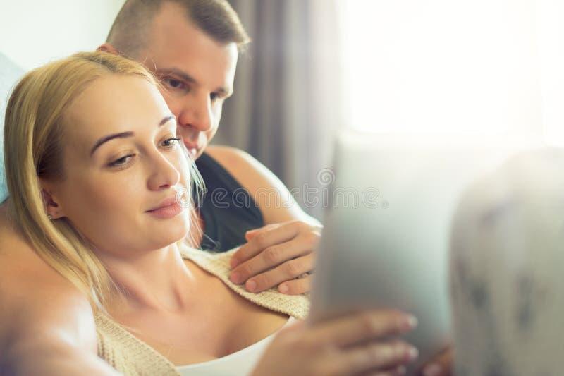 Elegancka para cuddling na kanapie używać cyfrową pastylkę przy ich nowożytnym domem Kobiety mienia pastylka, wyszukuje sieć zdjęcie royalty free