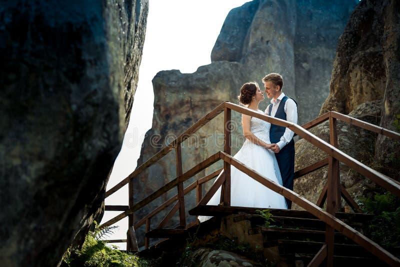 Elegancka para małżeńska właśnie tenderly trzyma ręki podczas gdy stojący na drewnianych schodkach między dwa skałami pogodny obrazy royalty free