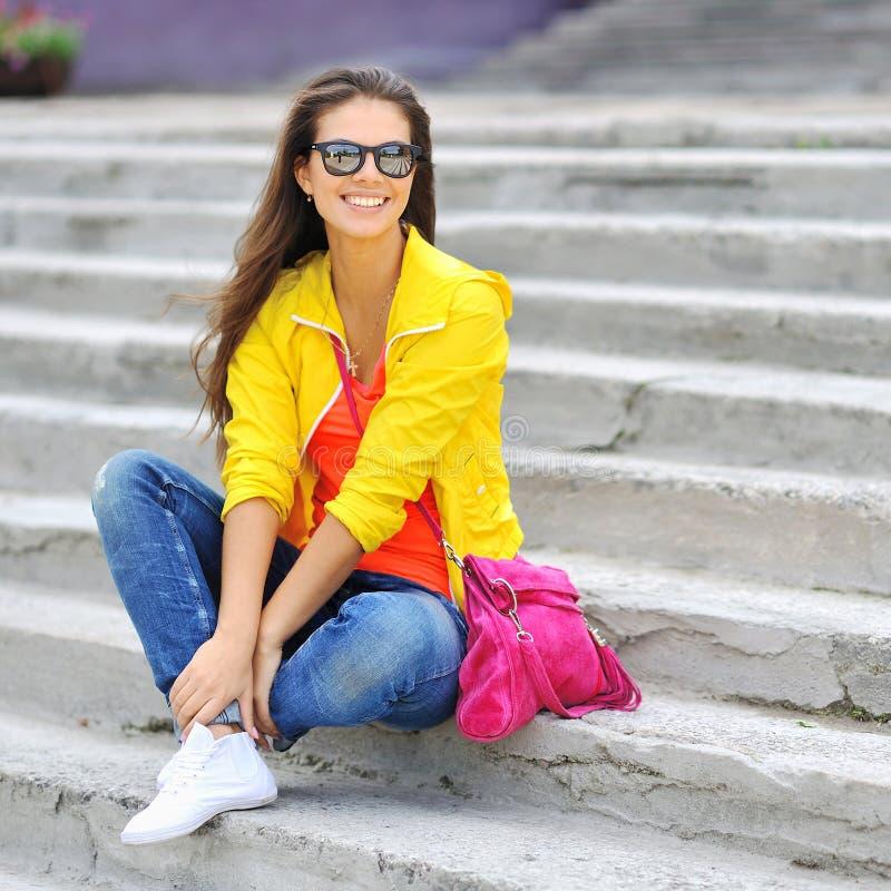 Elegancka piękna dziewczyna jest ubranym okulary przeciwsłonecznych w kolorowych ubraniach zdjęcia royalty free
