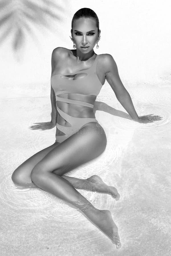Elegancka seksowna kobieta w zadziwiającym bikini na garbnikującym szczupłym i foremnym ciele pozuje blisko basenu czarny white zdjęcia stock