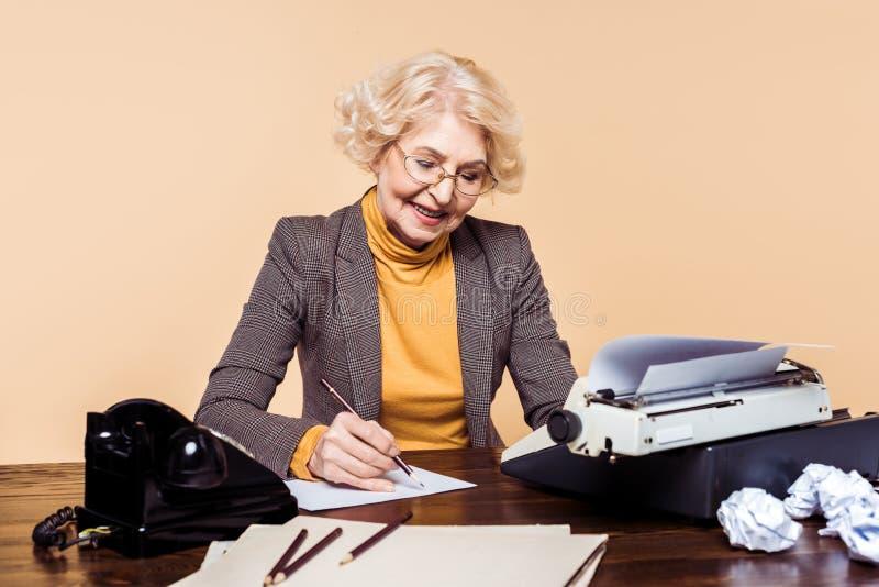 elegancka starsza kobieta pisze na papierze przy stołem z maszyną do pisania zdjęcie royalty free
