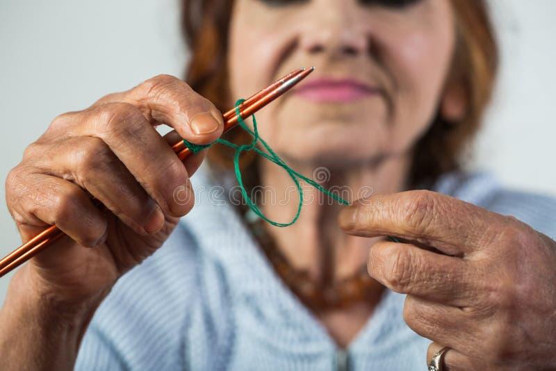 _ Elegancka starsza kobiety mienia igła i wełna w ręce i robimy dzianiu podczas jej czasu wolnego Seniour dama dalej zdjęcie stock