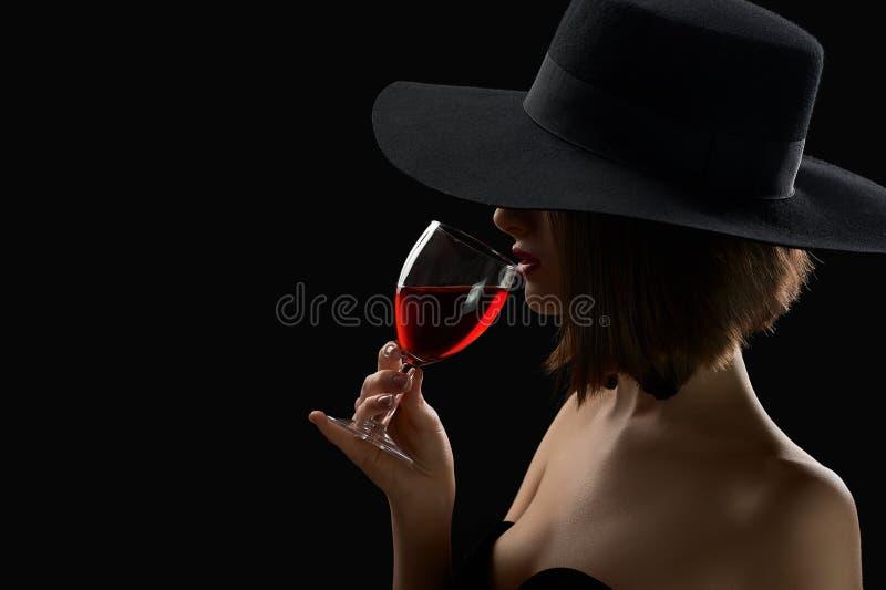 Elegancka tajemnicza kobieta w kapeluszowym mieniu szkło czerwone wino dalej obrazy royalty free