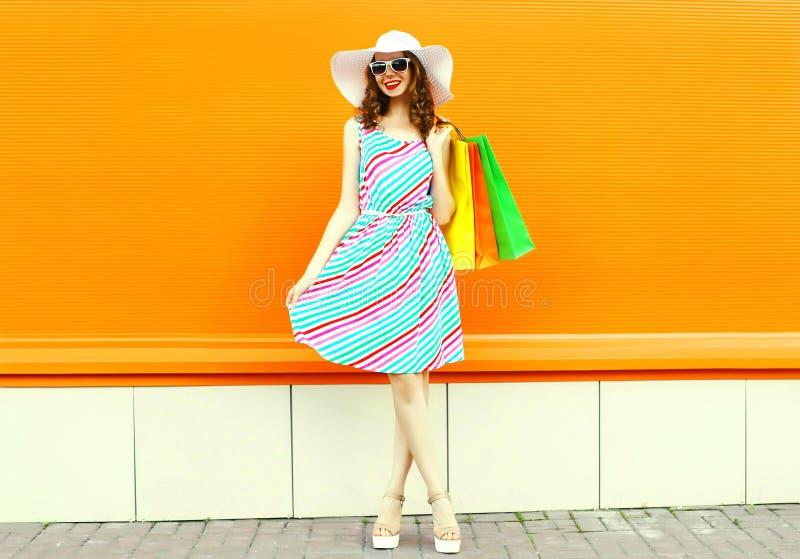 Elegancka uśmiechnięta kobieta jest ubranym kolorową pasiastą suknię z torbami na zakupy, lato słomiany kapelusz pozuje na pomara obrazy royalty free