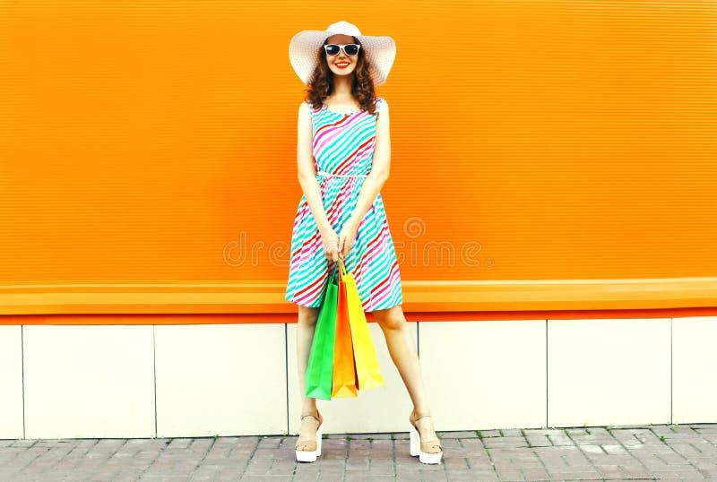 Elegancka uśmiechnięta kobieta jest ubranym kolorową pasiastą suknię z torbami na zakupy, lato słomiany kapelusz pozuje na pomara fotografia stock
