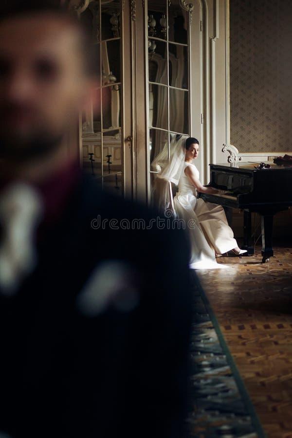 Elegancka wspaniała panna młoda bawić się eleganckiego handso i fortepiano obrazy royalty free