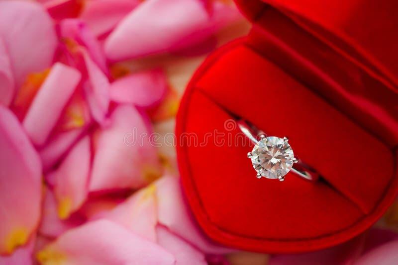 Elegancki ślubny diamentowy pierścionek w czerwonym kierowym biżuterii pudełku na pięknym menchii róży płatka tle obrazy stock