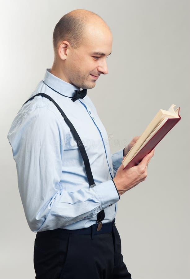 Elegancki łysy mężczyzna czyta książkę fotografia stock