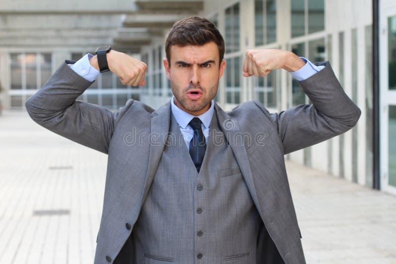 Elegancki śmieszny biznesmen napina jego mięśnie zdjęcie royalty free