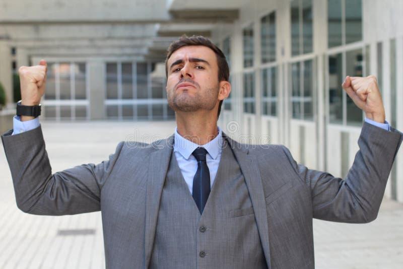 Elegancki śmieszny biznesmen napina jego mięśnie fotografia royalty free