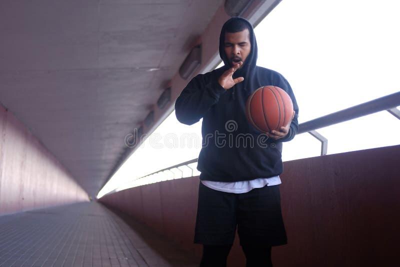 Elegancki afroamerykański facet jest ubranym czarnego hoodie trzyma ziewanie i koszykówkę zdjęcia stock