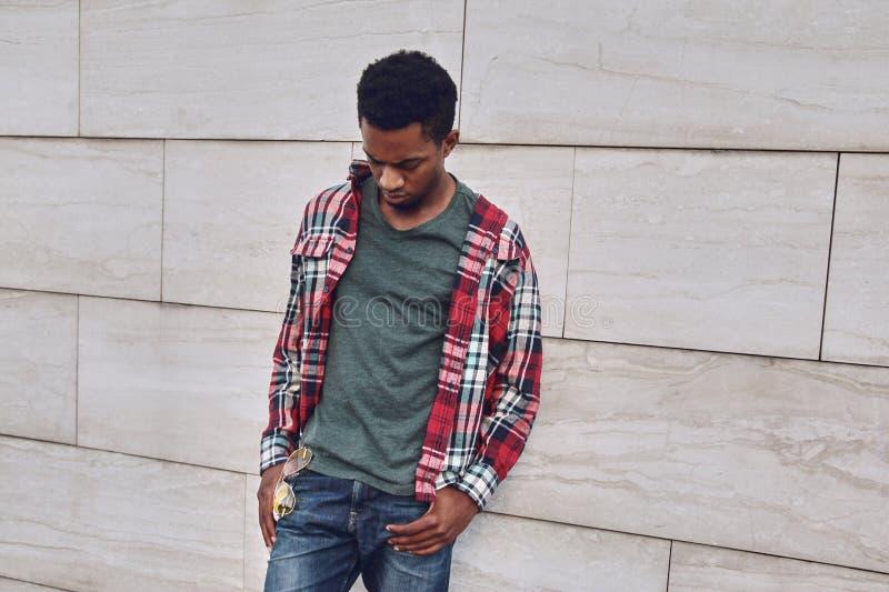 Elegancki afrykański mężczyzna jest ubranym czerwoną szkockiej kraty koszula patrzeje w dół, młody facet pozuje na miasto ulicie, obraz stock