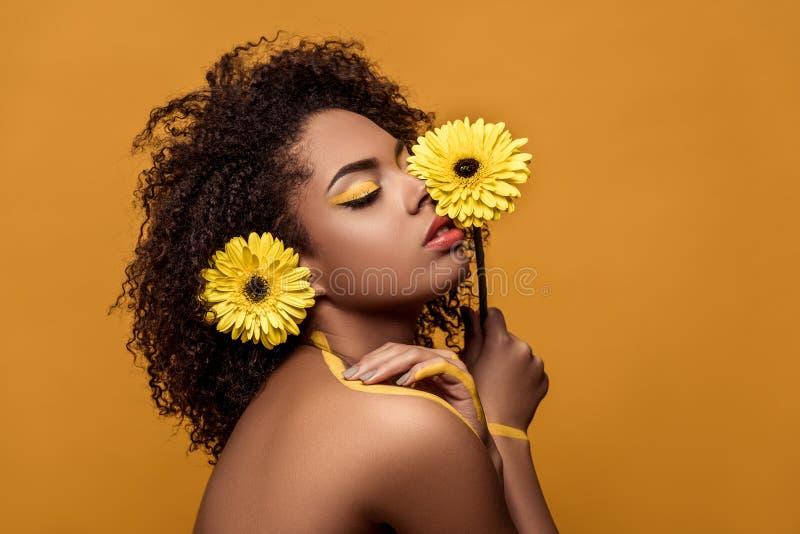 Elegancki amerykanin afrykańskiego pochodzenia dotyka jej skórę kobieta z artystycznymi makijaży chwytami kwitnie jej twarzą tend obraz royalty free