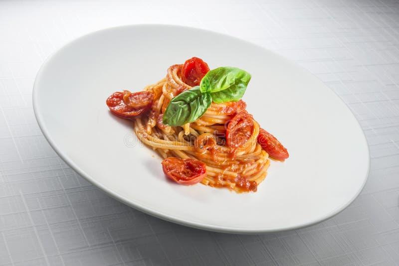 Elegancki Biały round talerz z spaghetti basilem i pomidorem obrazy stock