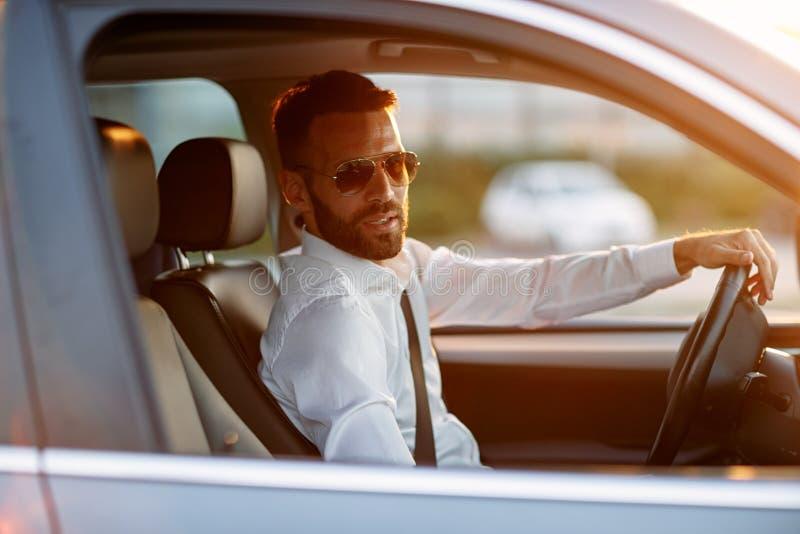 Elegancki biznesmen jest ubranym okulary przeciwsłonecznych podczas gdy jadący samochód obrazy stock