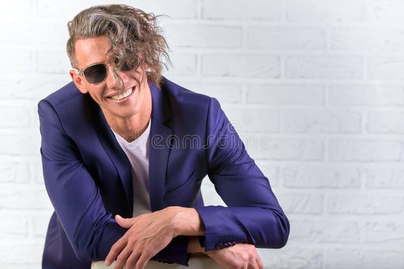 Elegancki biznesmen siedzi na krześle na białym tle z kędzierzawy długie włosy w okularach przeciwsłonecznych zdjęcie stock