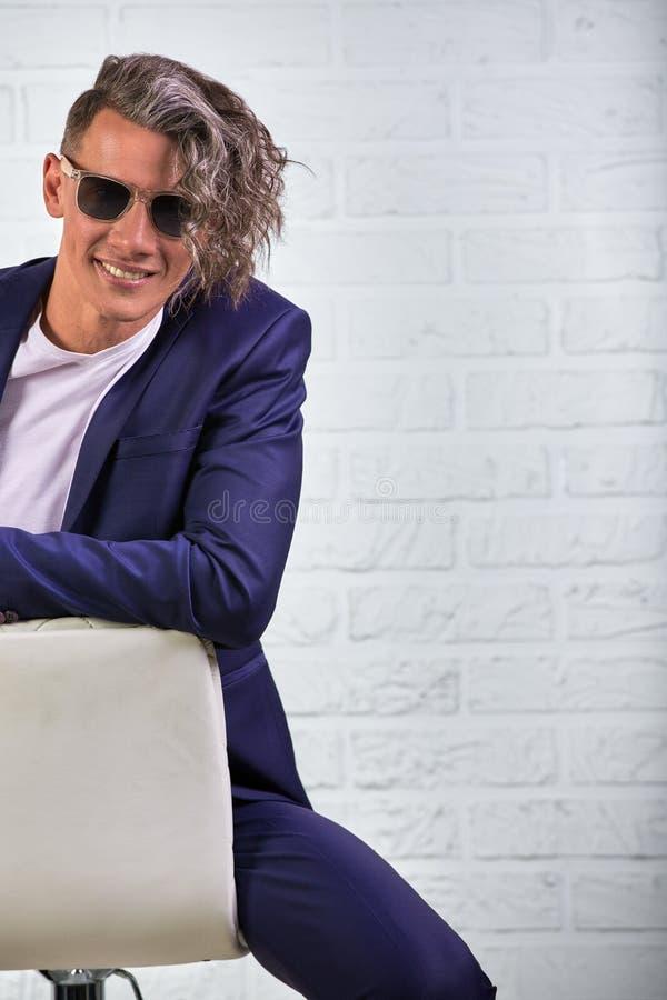 Elegancki biznesmen siedzi na krześle na białym tle z kędzierzawy długie włosy w okularach przeciwsłonecznych obraz stock
