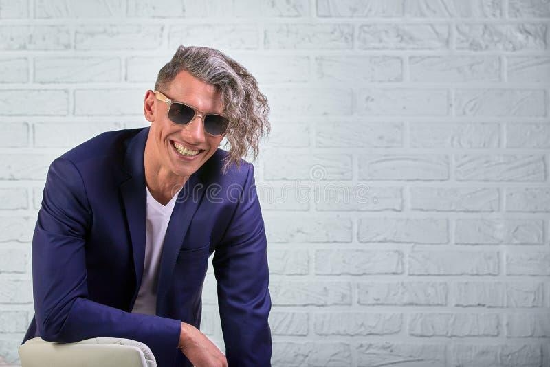 Elegancki biznesmen siedzi na krześle na białym tle z kędzierzawy długie włosy w okularach przeciwsłonecznych zdjęcia royalty free