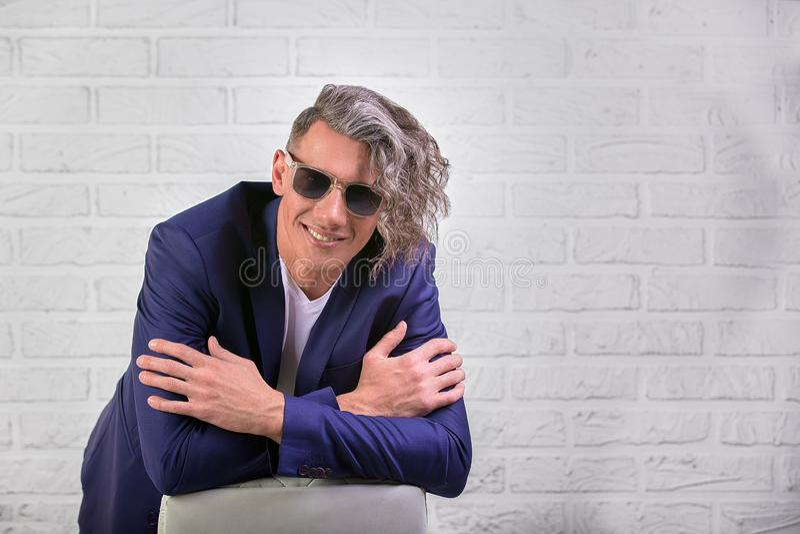 Elegancki biznesmen siedzi na krześle na białym tle z kędzierzawy długie włosy w okularach przeciwsłonecznych obrazy royalty free