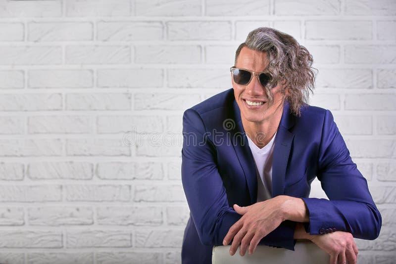 Elegancki biznesmen siedzi na krześle na białym tle z kędzierzawy długie włosy w okularach przeciwsłonecznych fotografia royalty free