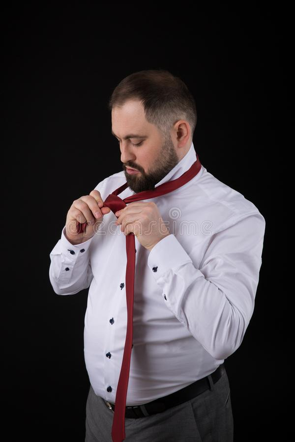 Elegancki biznesmen w białej koszula, prostuje krawaty jego krawata ob czerni tło zdjęcie stock