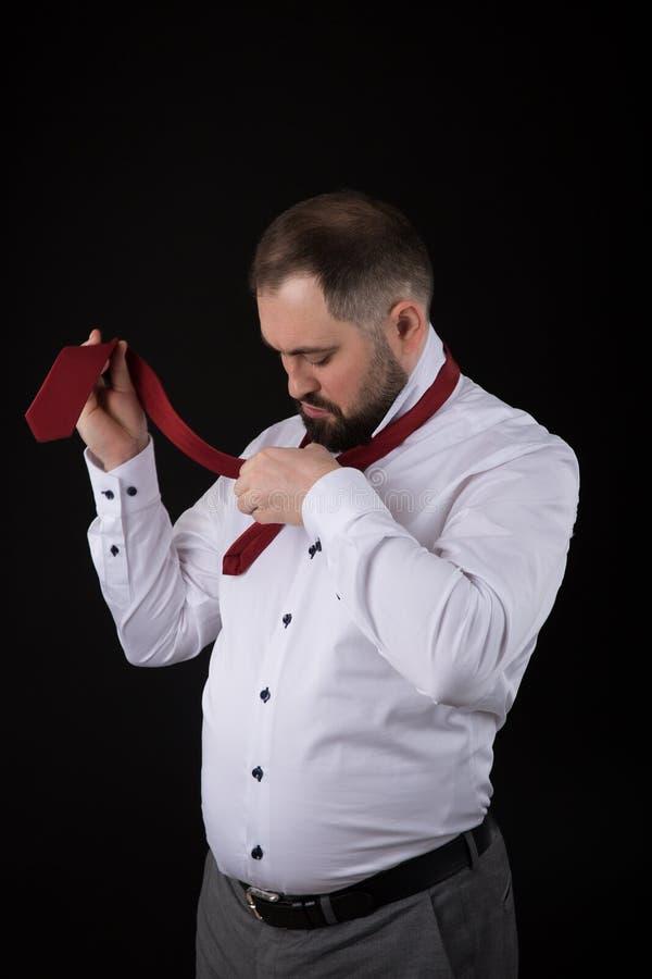 Elegancki biznesmen w bia?ej koszula, prostuje krawaty jego krawata ob czerni t?o obraz stock