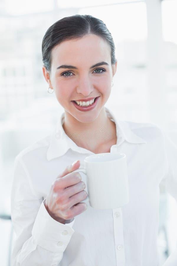 Elegancki bizneswoman trzyma filiżankę w biurze zdjęcie royalty free