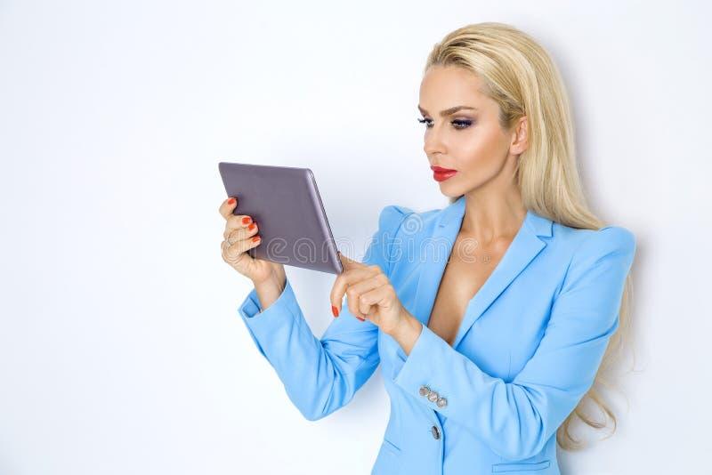 Elegancki bizneswoman trzyma pastylkę w kurtce zdjęcia stock