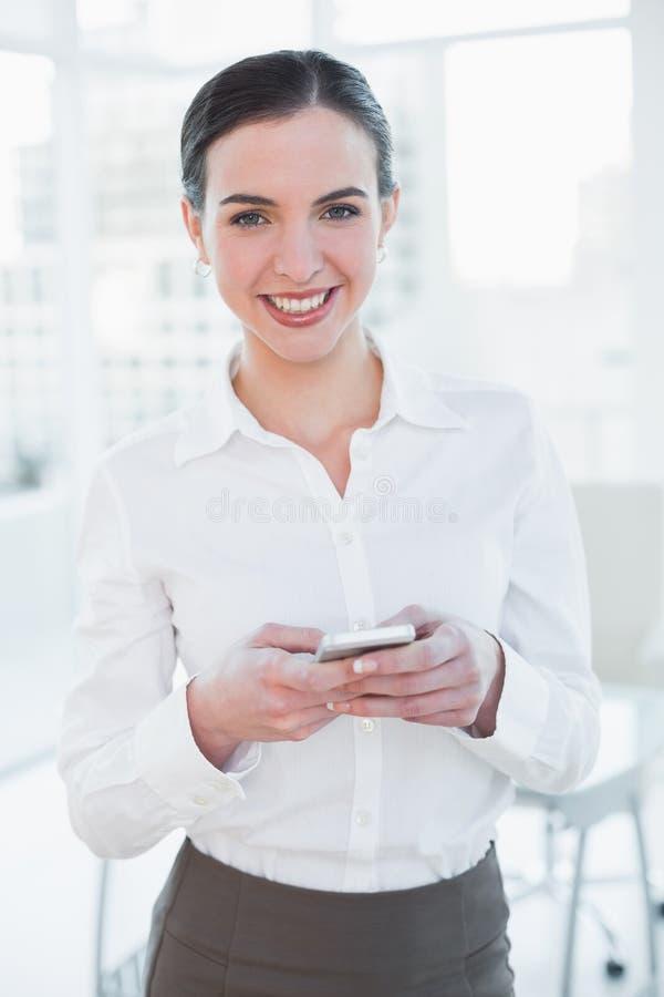 Elegancki bizneswoman z telefonem komórkowym w biurze zdjęcia stock