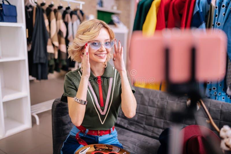 Elegancki blogger ono uśmiecha się podczas gdy pokazywać jej zwolennikom nowych okulary przeciwsłonecznych obrazy stock