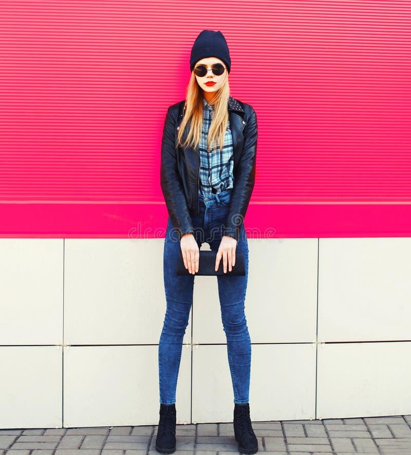 Elegancki blondynki kobiety model w długiej pozuje jest ubranym rockowej czerń stylu kurtce, kapelusz, z torebki sprzęgłem na mia zdjęcia stock