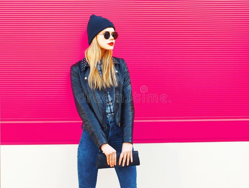 Elegancki blondynki kobiety model w profilowym patrzejący daleko od jest ubranym rockową czerń stylu kurtkę, kapelusz, z torebki  fotografia royalty free