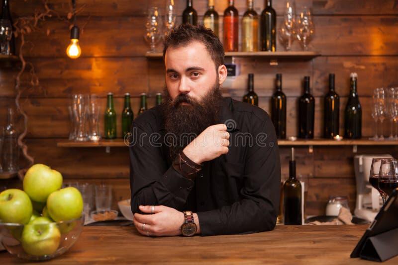 Elegancki brodaty barman w koszula przy prętowym odpierającym tłem zdjęcie stock