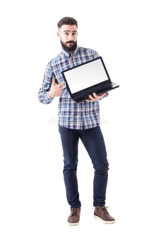 Elegancki brodaty młody człowiek wskazuje palec na pustym laptopu ekranie patrzeje kamerę zdjęcie stock