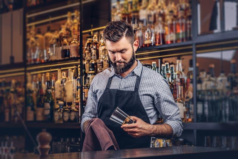Elegancki brutalny barman czyści szkło z płótnem przy baru kontuaru tłem obraz royalty free