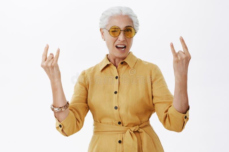 Elegancki chłód i wspaniała babcia z popielatym włosy w modnych żółtych okularach przeciwsłonecznych i żakieta seansu skały n rol zdjęcia royalty free