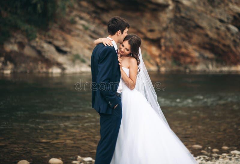 Elegancki delikatny elegancki fornal i panna młoda blisko rzeki z kamieniami Ślubna para w miłości obrazy stock
