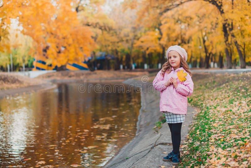 Elegancki dziecko dziewczyny 5-6 roczniak jest ubranym modnego menchia żakiet w jesień parku patrzeć kamerę jesień spadek lasowej obraz stock