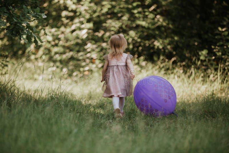 Elegancki dziewczynki 2-5 roczniak trzyma dużego balon jest ubranym modne menchie ubiera w łące figlarnie fotografia royalty free