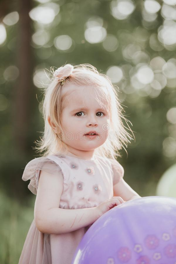 Elegancki dziewczynki 2-5 roczniak trzyma du?ego balon jest ubranym modne menchie ubiera w ??ce figlarnie fotografia stock