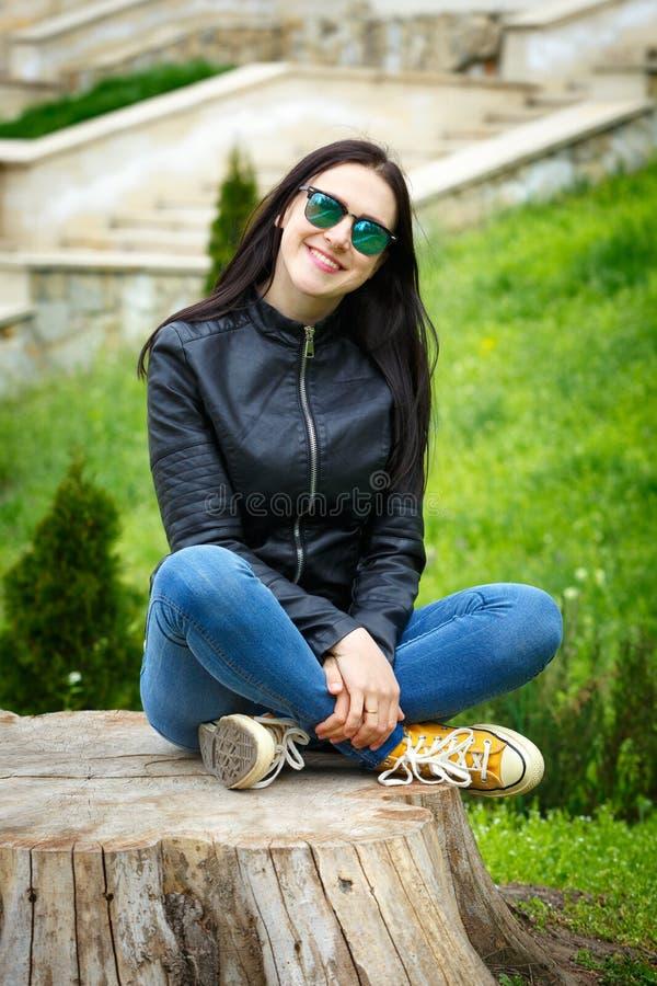 Elegancki dziewczyny obsiadanie na starym fiszorku Szczęśliwa modniś kobieta relaksuje na naturze zdjęcie stock
