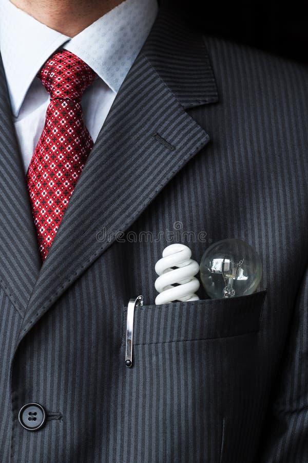 Elegancki elegancki biznesmen utrzymuje dwa żarówki i fluorescencyjnej wydajność energii w jego piersi kieszeni - Płonącą - obraz stock