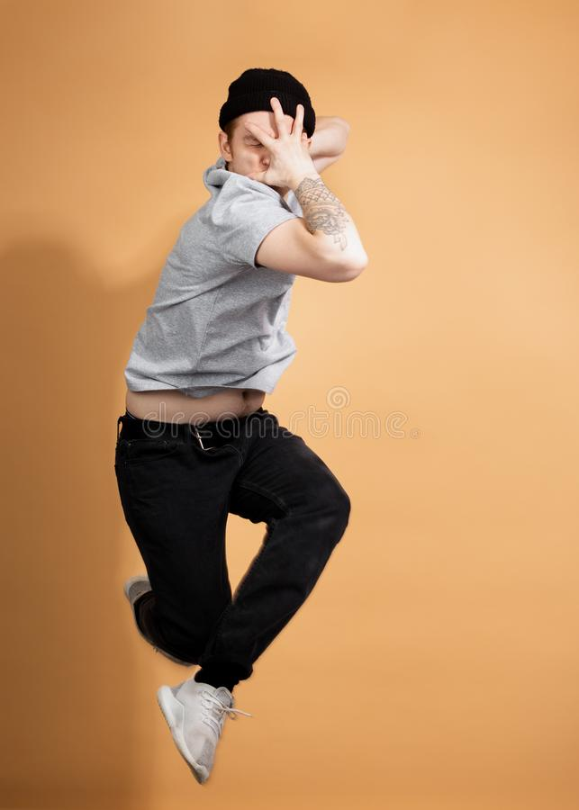 Elegancki facet ubierający w szarej koszula, czarnych cajgach i czarnym kapeluszu z tatuażem na jego ręce, skacze na beżu obraz stock