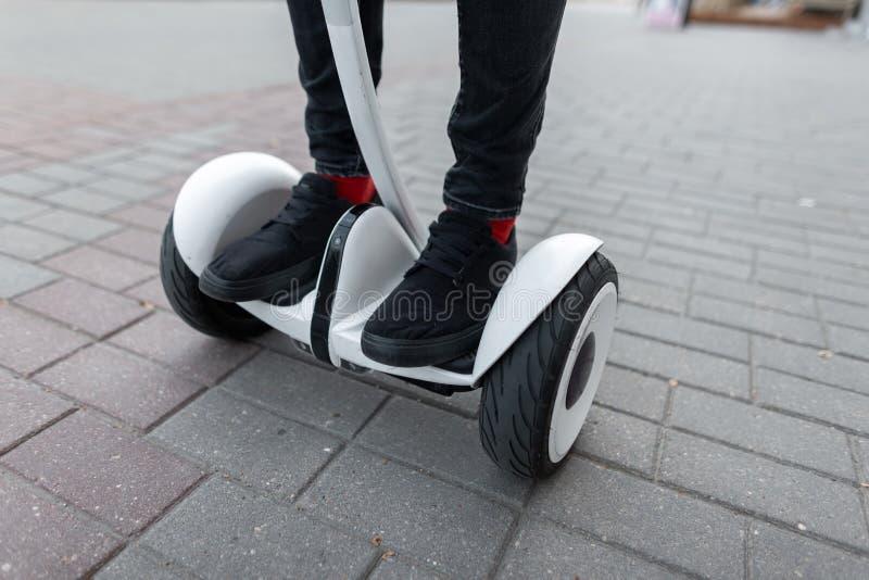 Elegancki facet w cajgach w sneakers w czerwonych skarpetach jedzie a na białym hoverboard wokoło miasta na letnim dniu Zbliżenie obrazy stock