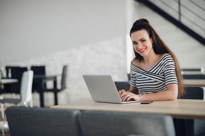Elegancki i rozochocony bizneswoman Rozochocona młoda piękna kobieta jest przyglądającym kamerą z uśmiechem podczas gdy siedzący  obraz royalty free
