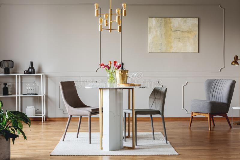 Elegancki jadalni wnętrze z złotymi akcentami, stołem, krzesłami i obrazem na ścianie, zdjęcie stock