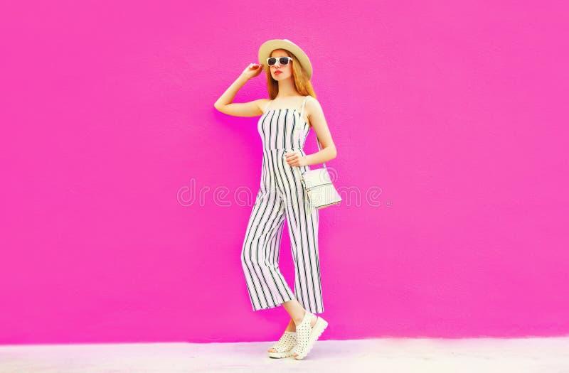 Elegancki kobieta model w lata round słomianym kapeluszu, biały pasiasty kombinezon pozuje na kolorowej menchii ścianie obrazy stock