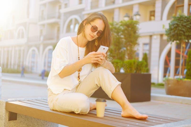 Elegancki kobiety obsiadanie na ławce z smartphone obrazy royalty free