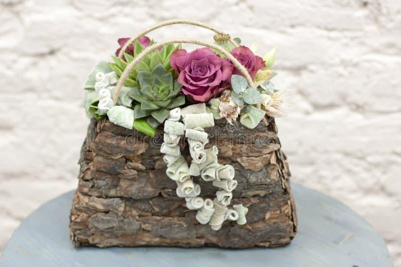 Elegancki kwiecisty skład w postaci torby stojaków na błękitnym drewnianym stole zdjęcie stock