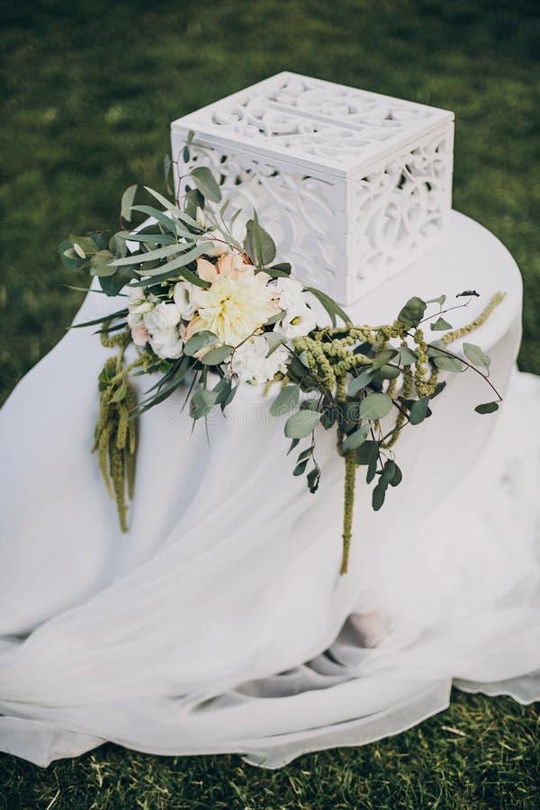 Elegancki kwiecisty wystrój ślubna nawa, różani płatki na trawie i nowożytny drewniany pudełko dla prezentów od gości dla poślubi obraz stock